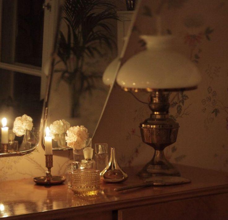 Lampa och tänt ljus i skymningsljus.