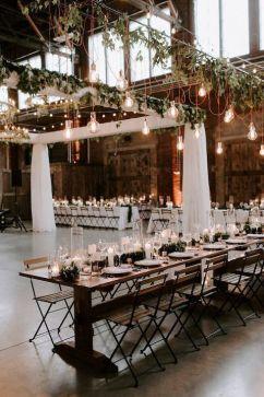 Casamento industrial com mesas comunitárias e varal de lâmpadas. Decoração elegante, incluindo velas e castiçais. #wedding #decoracaodecasamento #weddingdecor #stringlightswedding #industrialwedding #casamentoindustrial