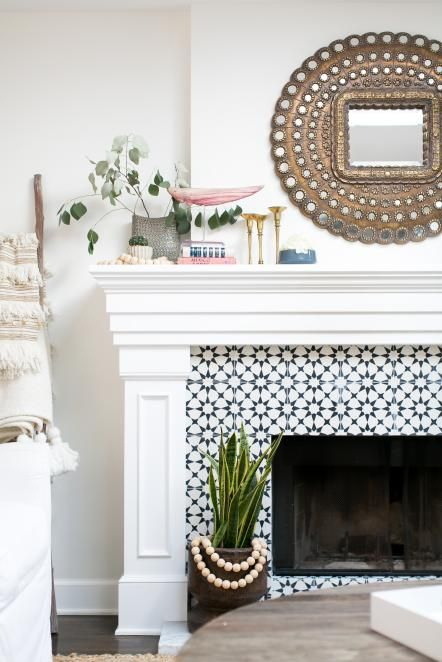 In this modern home from designer Ashley Clark, clean white walls and furniture become a canvas for layers of vivid color and pattern. Rugs, throws and even a patterned backsplash in the fireplace bring energy and interest to the stylish, monochromatic setting.
