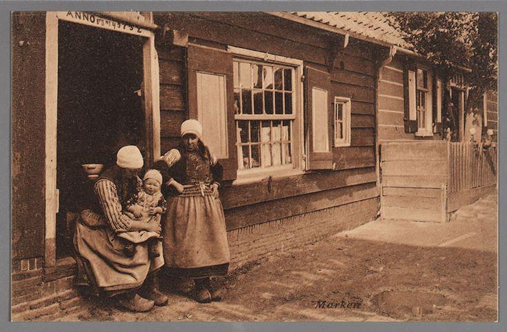 Twee vrouwen in Marker dracht en een klein kind poseren in de deuropening. 1905-1915 #NoordHolland #Marken