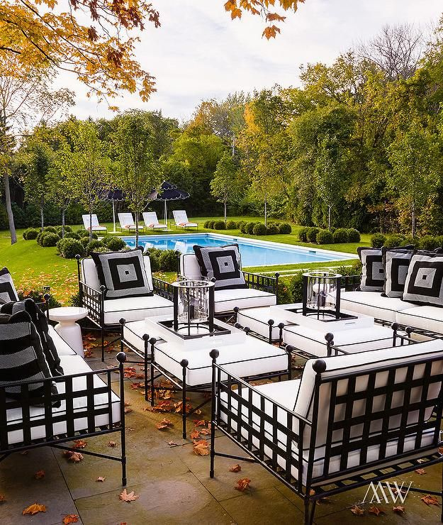 Chic patio features wrought iron sofas, chairs and ottomans covered in black and white cushions ...