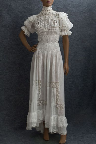Circa 1905 tea dress made from white cotton dotted swiss, the dress is elaborately embellished with lace, embroidered cut work, ruffles, and rows of narrow tucks so beloved by the Edwardians. It closes in back with loops and small mother-of-pearl buttons. The puffed sleeves have inner cords to hold them in place. The skirt is longer and fuller in back, forming a small train. Via Vintage Textile.