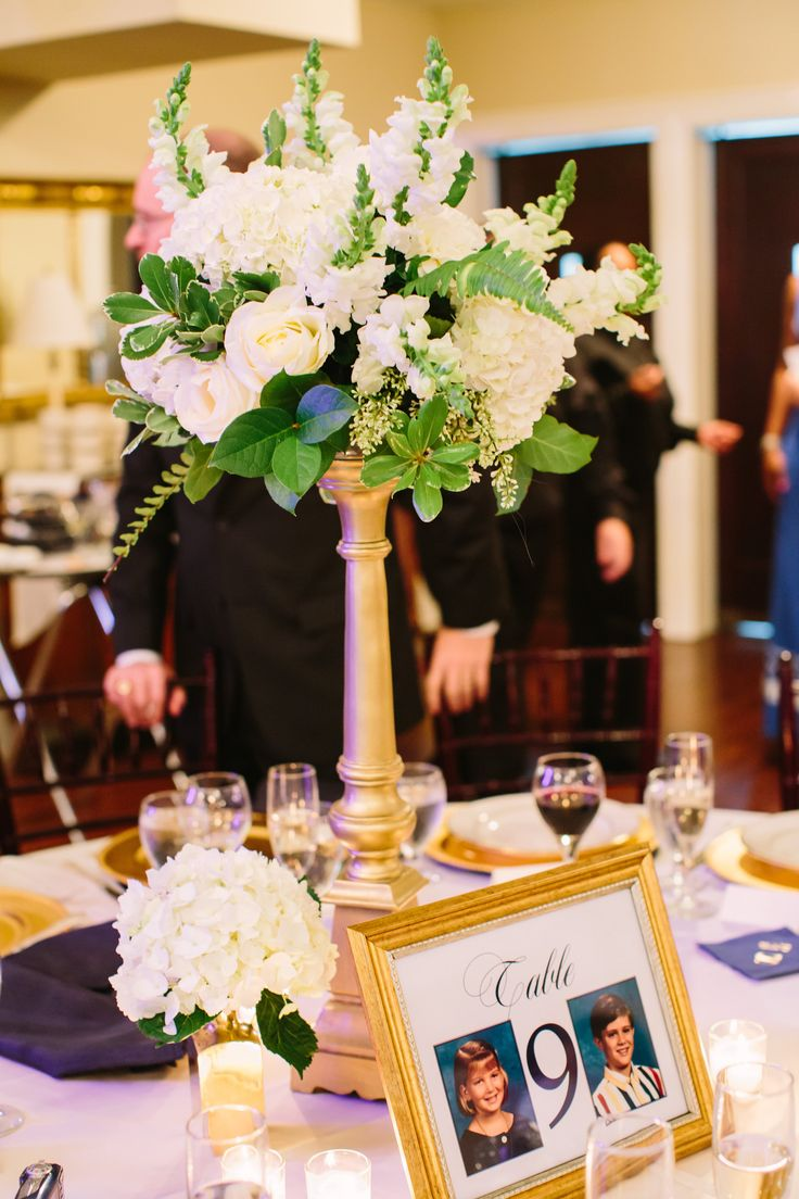 tall wedding reception centerpieces of white and green featured hydrangea, roses,  snapdragons, fern and  lemon leaf on tall gold pedestals, paired with a single hydrangea in a gold julep cup.