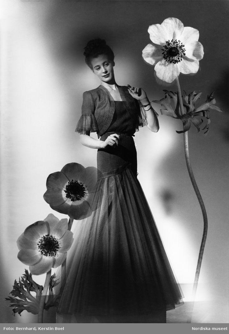 Vårmodell för Idun i aftonklänning med kort jacka. Stora blommor runt modellen.  Fotograf: Kerstin Bernhard, ca 1945-1950