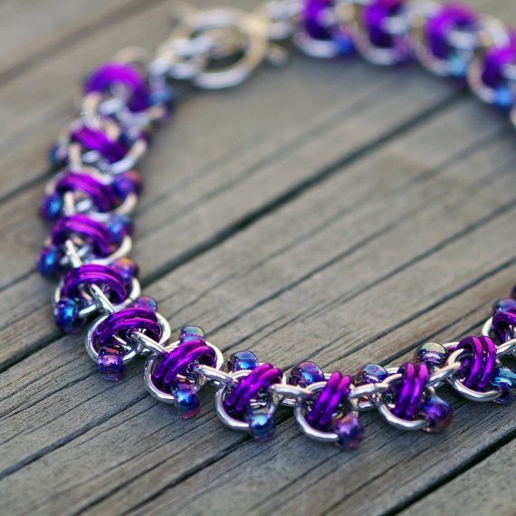 This purple and silver beaded chain maille bracelet combines bright silver and purple anodized aluminum jump rings with iridescent purple glass