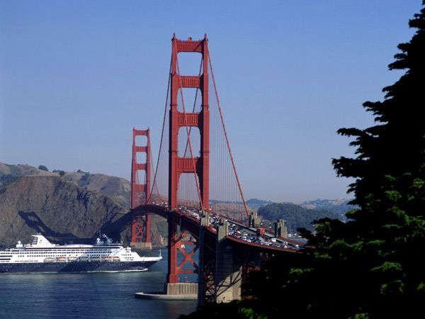 A cruise ship glides easily under the Golden Gate Bridge. At its center the suspension span is some 265 feet above the average high-water mark.