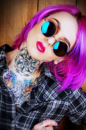 Primer plano retrato de una chica moderna con el pelo brillante carmes y gafas de sol redondas  Foto de archivo