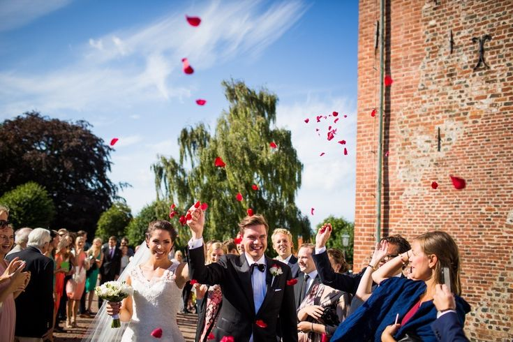 Wedding guests throwing rose petals on a newlywed couple