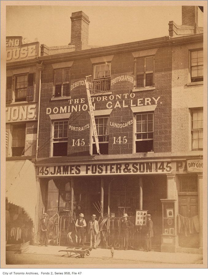 145 King Street East – (c.1870) – Showing the James Foster & Son general hardware store, and photographer D.C. Butchart's Toronto Dominion Gallery, which was located on the second floor.