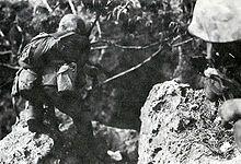 Battle of Saipan - Holding a Colt M1911, a Marine moves cautiously through the jungle of Saipan. July 1944.