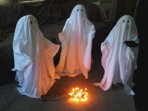 How cool and creepy are these ghost decorations?! At night it would look so awesome to see the lights flickering with a bunch of ghosts in a circle. White plastic tablecloths Styrofoam ball Stake Orange christmas lights Stick a stake in the ground with a Styrofoam ball for the head then cover it with the …