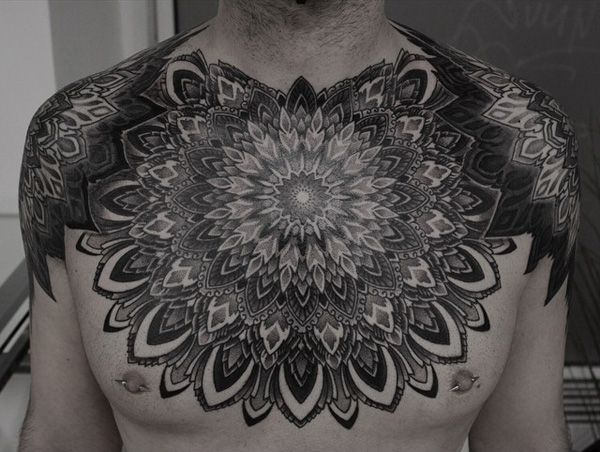 Mandala chest tattoo - Gorgeous looking black mandala tattoo. This style fills the person's chest and arms creating an illusion of a group of mandalas as his medals.