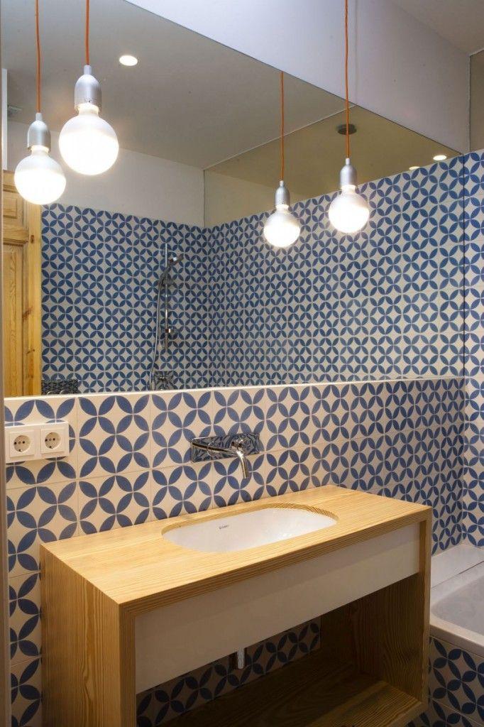 Un carrelage aux jolies couleurs blanches et bleues pour habiller la salle de bains et trancher avec le dépouillement du lavabo et des ampoules.