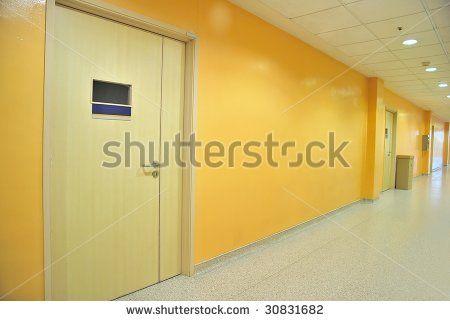 Closed doors along a lighted corridor - stock photo
