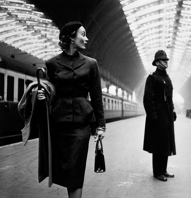 Toni Frissell: Victoria Station, London, 1951    Fashion model (identified as Lisa Fonssagrives) with English bobby on platform at London's Victoria Station (or not? See comment below). Photograph by Toni Frissell (one of the most celebrated female photographers of the 20th Century), published by Harper's Bazaar in 1951.