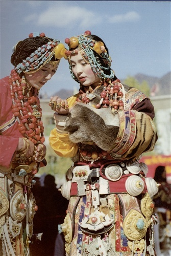 King Gesar Arts Festival in Kardze, Kham, Tibet 2003 | Two women from Pelyul, easily recognised by their headdresses. The woman on the right is the same as the previous several photo. The bead worn this lady's wears in the centre of her forehead is almost definitely an ancient dZi. dZi in her other jewelry, such as the rings she wears, may also be ancient beads