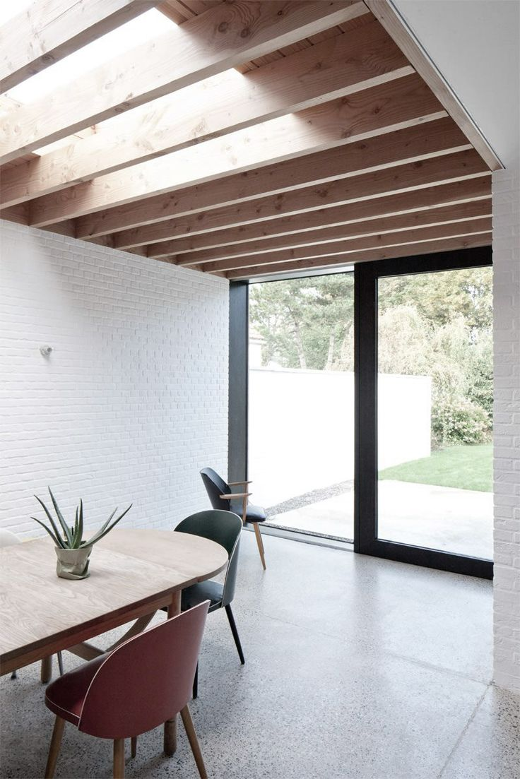 A mid-century modern dining area sits adjacent to the backyard, with wooden ceiling, white …