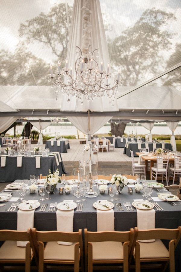 Steel gray tablecloth with all white and glass setting. Outdoor Wedding Reception