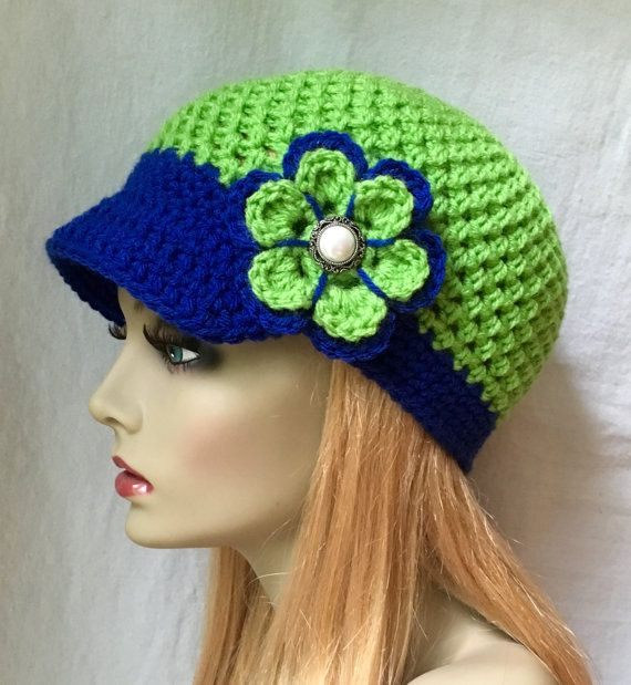 Slouchy Beret. Seahawk Blue with Lime Green (shown). Girls, Teens or Women's Hat. Hand-crocheted with beautiful acrylic yarn embellished with a Crocheted Flower. Buttons can be substituted per request. Warm and fun. Want this hat in a custom color? Just let me know. COLOR (S): Hat: Seahawk Lime Green and Blue. Let me know if you prefer a darker (navy blue) instead. Message me if youd like a custom color. Accents: A crochet Flower in Lime Green.  AVAILABLE SIZE(S):  Typical Size Chart  21…