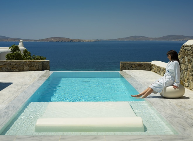 Mykonos Grand, Grand Suite with Private Pool: These two bedroom suites set at the two edges of the hotel property to offer privacy and views of the Aegean Sea. They feature a large furnished terrace with infinity private pool, barbecue setup, lounge chairs and a dining area shaded with a pergola.