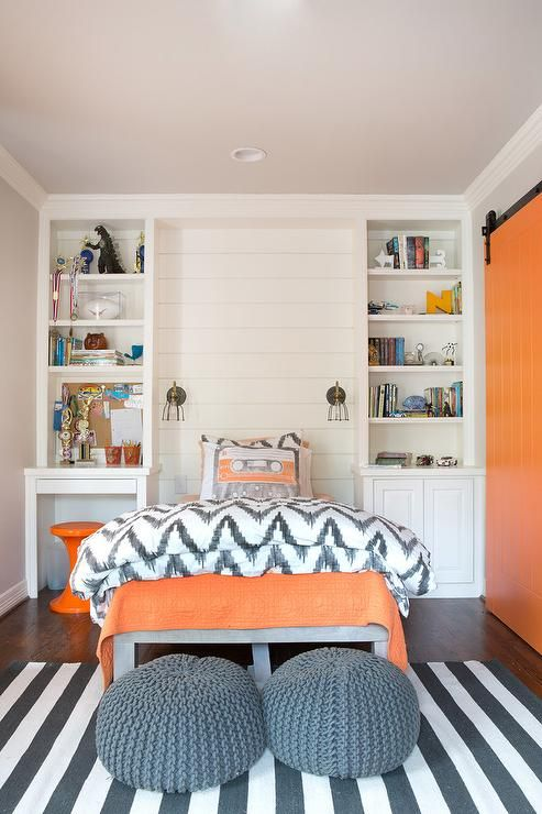 source: Evensen Design website Orange and gray boy's bedroom features a shiplap accent wall lined with a gray platform bed dressed in orange bedding and a West Elm Organic Chevron Duvet and Sham flanked by built-in bookcases with a desk to the left and cabinets to the right. Contemporary boy's room boasts a gray twin bed illuminated by cage sconces alongside a pair of gray knitted poufs placed at the foot of the bed atop a charcoal gray striped rug situated across from an orange barn door…