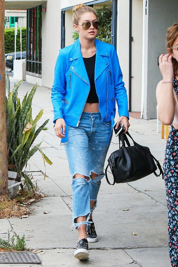 Gigi Hadid wears a black crop top with her distressed boyfriend jeans, blue leather jacket, sneakers and black bag.
