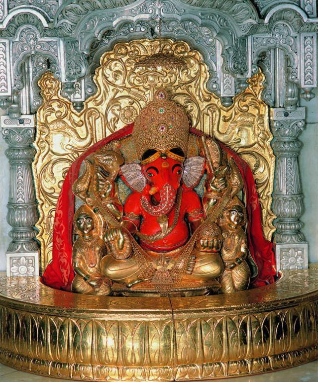 The idol of Shree Siddhivinayak was carved out of a single black stone and with the trunk on the right. This is rather unusual appearance of Lord Ganesh.On both sides of the Lord Ganesh idol, are placed one idol each of Riddhi and Siddhi goddesses who are appearing like peeping out of the Ganesh idol from behind.