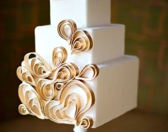 A simple, three-tiered square cake with ribbons of gold embellishments.  #TheLANEWeddings