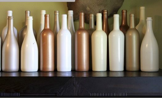painted wine bottles for use as vases. since the 50th anniversary is the golden, we could do shades of white, cream, matte gold, and glittery gold paints for a textured and varied look. we could put a single tall flower in each one and then line up on a table or shelf.