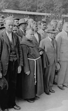 Still in their civilian clothes, newly arrived prisoners, among whom is a clergyman, stand at roll call in Buchenwald concentration camp.