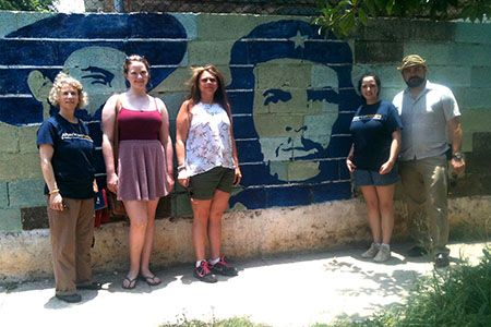 MCCC Study Abroad participants in Cuba, with a mural depicting figures from the country's revolution. Pictured, from left, are Professor Durso-Finley, Rachel Levitt, Jennifer Vitella, Bridget Phelan and Brendon Pearsall.
