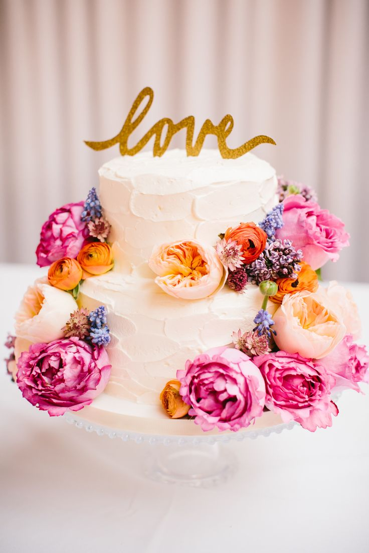 """Flower covered cake with gold """"love"""" topper."""