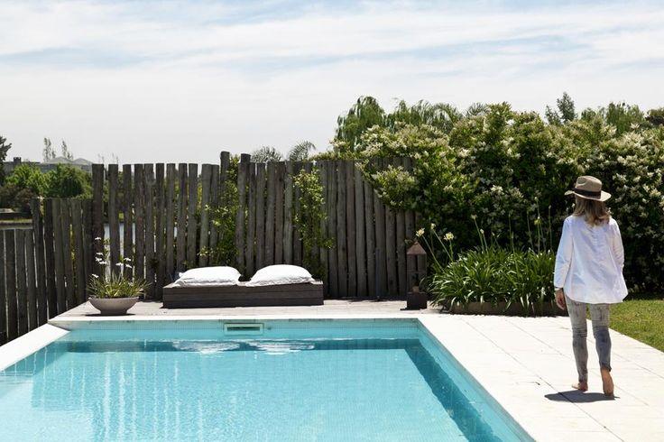 """La pileta con borde """"sin fin"""" se une visualmente a la laguna. A su alrededor, un gran camastro de madera de lapacho para disfrutar de los días al sol. / Magalí Saberian"""
