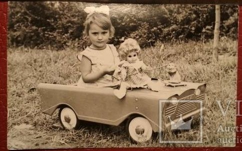 Девочка в машинке с куклой и бантом