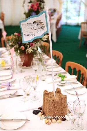 Sand castles, shells and flags for beach themed wedding tables names/centres