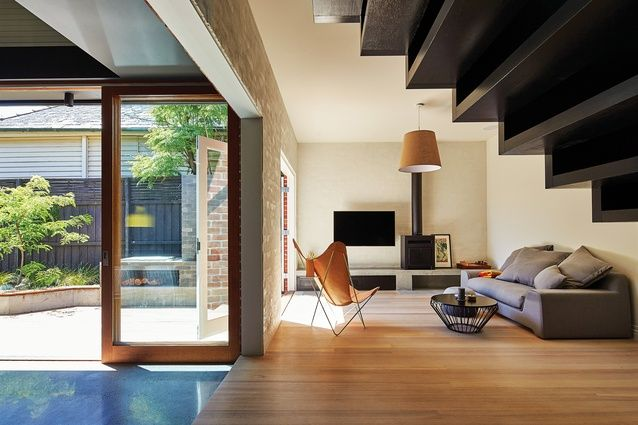 The edge of the existing house has been retained, with a red brick wall running through the living spaces.