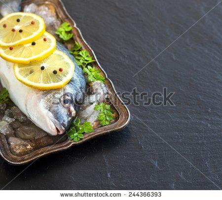 Fresh dorado fish on ice on vintage silver tray
