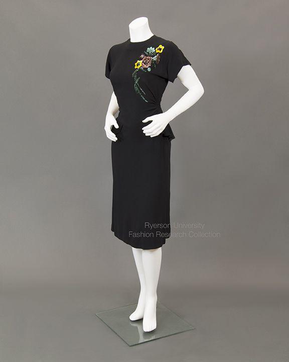 Black crepe dress with short sleeves, peplum waist detail, back ties, floral sequin spray across left shoulder, c.1940s. FRC1993.04.010