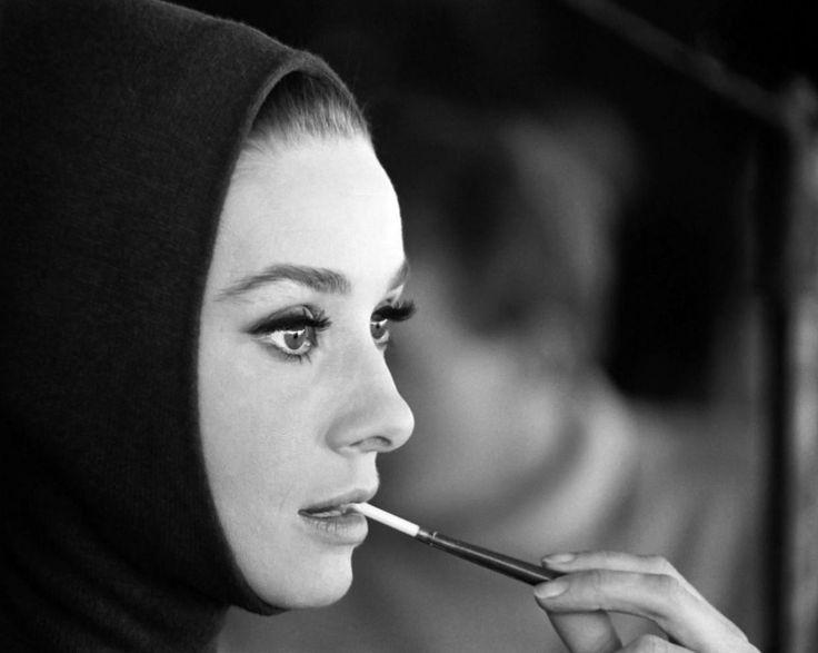 """La actriz Audrey Hepburn fotografiado por Vincent Rossell en los estudios de Boulogne, ubicado en la avenida Jean-Baptiste-Clément, en Boulogne-Billancourt, una comuna francesa en el departamento de Hauts-de-Seine, en la región de Île-de-France, en el suburbios del oeste de París, durante un descanso en una sesión de fotos para el material de publicidad de su nueva película """"Charada"""", en enero de 1963. Audrey llevaba puesto: Equipo de esquí: Givenchy (mono de un tejido liso marrón de punto…"""