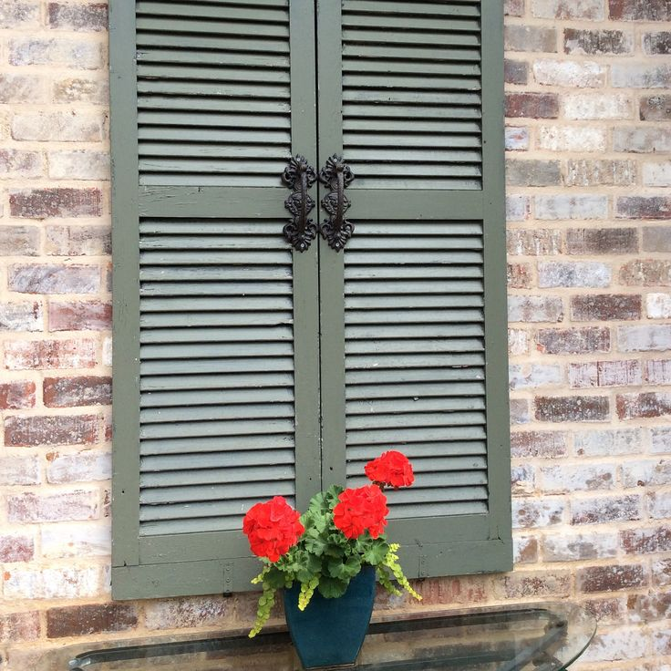 Exterior Wall Hardware : Antique shutters painted green mounted on outdoor brick