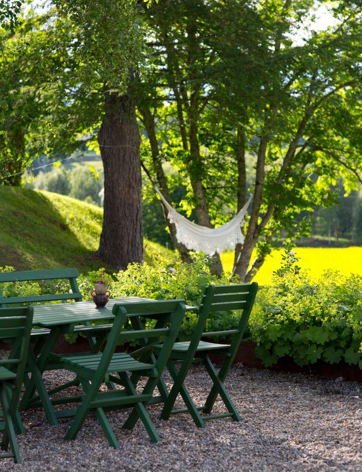 Gammaldags trädgårdsgrupp och trädgård med grusplan och hängmatta