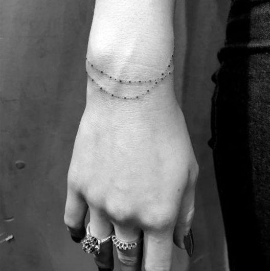 tatouage femme bracelet poignet, une enfilade de petites perles noirs, un bijou élégant, bagues