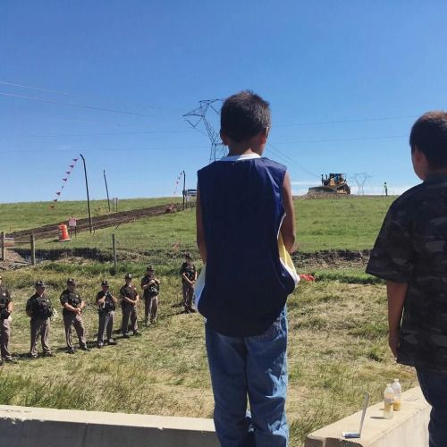 Two Young Lakota boys watch as the construction equipment is...