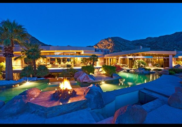 Falling Rock Lane, Indian Wells, CA    Suspended over a pond gushing water into 19 waterfalls, this contemporary desert manse has living and dining rooms that extend out through retractable glass walls to sun terraces that look out over a canyon. The master bathroom leads out to an outdoor shower and tanning area. And the patio boasts a resort-style swimming pool with swim up bar and fire pits.
