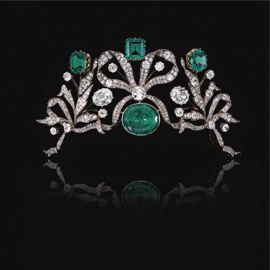 Emerald & diamond tiara designed as series of bows entwined with foliate sprays set with cushion-shaped & circular-cut diamonds, centring on an oval emerald surmounted by an octagonal emerald, a step-cut emerald & a hexagonal emerald, weighing respectively 7.58, 7.26 and 8.05 cts. Detachable tiara frame, the tiara can be worn as a devant de corsage & as a necklace centre. c. 1870.  Formerly the proprty of a Belgian princess.  Sold at auction for 420,000 CHF (before sale estimate of 280,000…