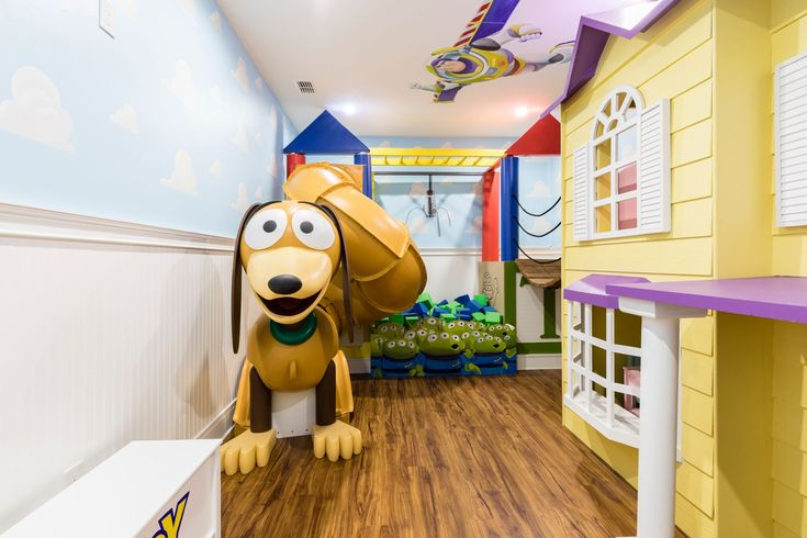 This Toy Story themed room is magical . It features a life size doll house and slinky slide . #toystory #suzannenicholsdesigngroup #playroom #slide #buzzlightyear #dollhouse