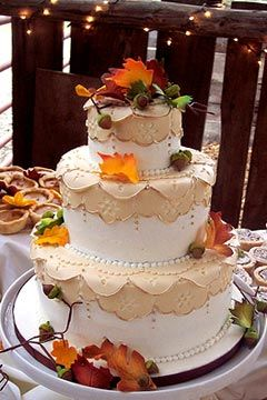 Romantic, three tier, white and beige, lacy wedding cake decorated with green, orange and yellow autumn leaves