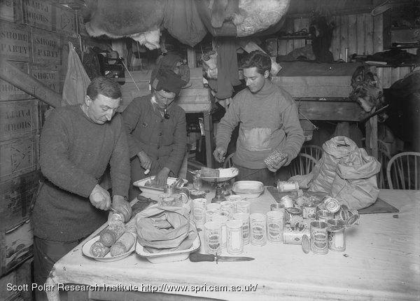 Dr Atkinson, Lieut. Bowers and Mr Cherry-Garrard cutting up pemmican.