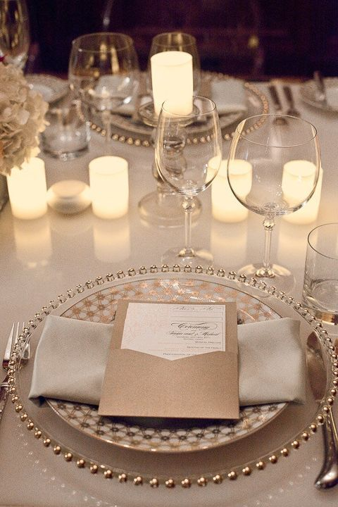 Layered Dishware in Gold and Cream with Menu on Top and Candlelight.