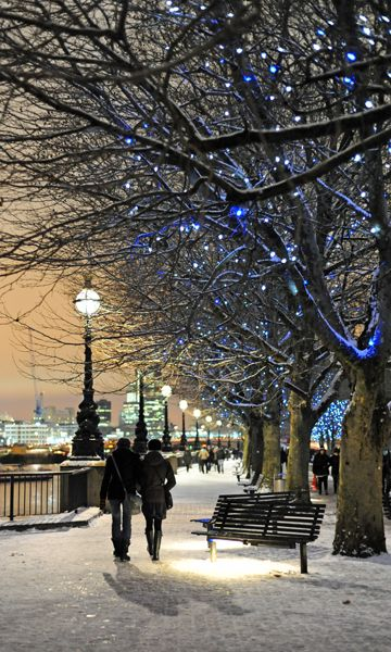 A young couple taking a romantic walk in the snow at dusk along the South Bank of the River Thames, London